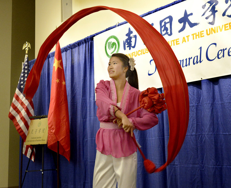 Nicole McCallum, with the Chinese and American Friendship Association of Maine, does a celebration dance during the inaugural ceremony for the Confucius Institute at the University of Southern Maine in Gorham on Wednesday, Sept. 25, 2013.