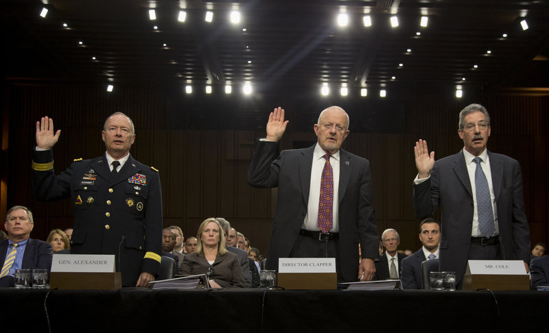 From left, NSA Director General Keith Alexander, Director of National Intelligence James Clapper and Deputy Attorney General James Cole are sworn before a hearing Thursday.