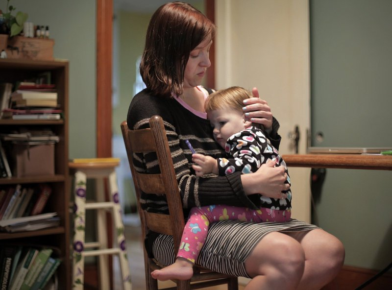 Erica Burkhart tends to her daughter Lumi Stone in her Portland home on Wednesday. Burkhart, a single mom attending graduate school, will buy her own insurance in the new marketplace opening Tuesday.
