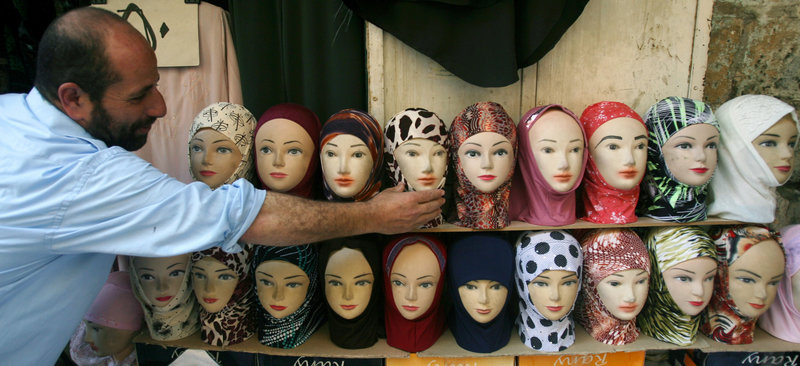 A Palestinian vendor adjusts a mannequin's head scarf outside his shop in the Old City of Jerusalem, during the Muslim holy month of Ramadan in this September 2007 photo. An expert notes that Americans stereotype women who wear such head scarves.