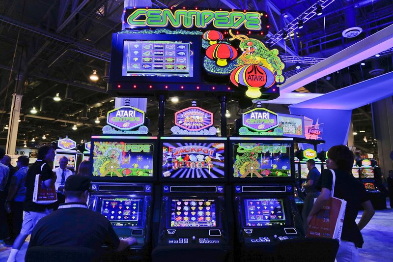 Gaming industry representatives play the Centipede video game slot machine at the Global Gaming Expo Wednesday in Las Vegas.