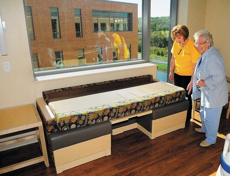 Nurse manager Edie Welch shows her mother, Lillian Merrill, how a couch in a patient room folds into a bed during a tour of the MaineGeneral Medical Center's new Alfond Center for Health. Each room features private rooms and space for family to stay.