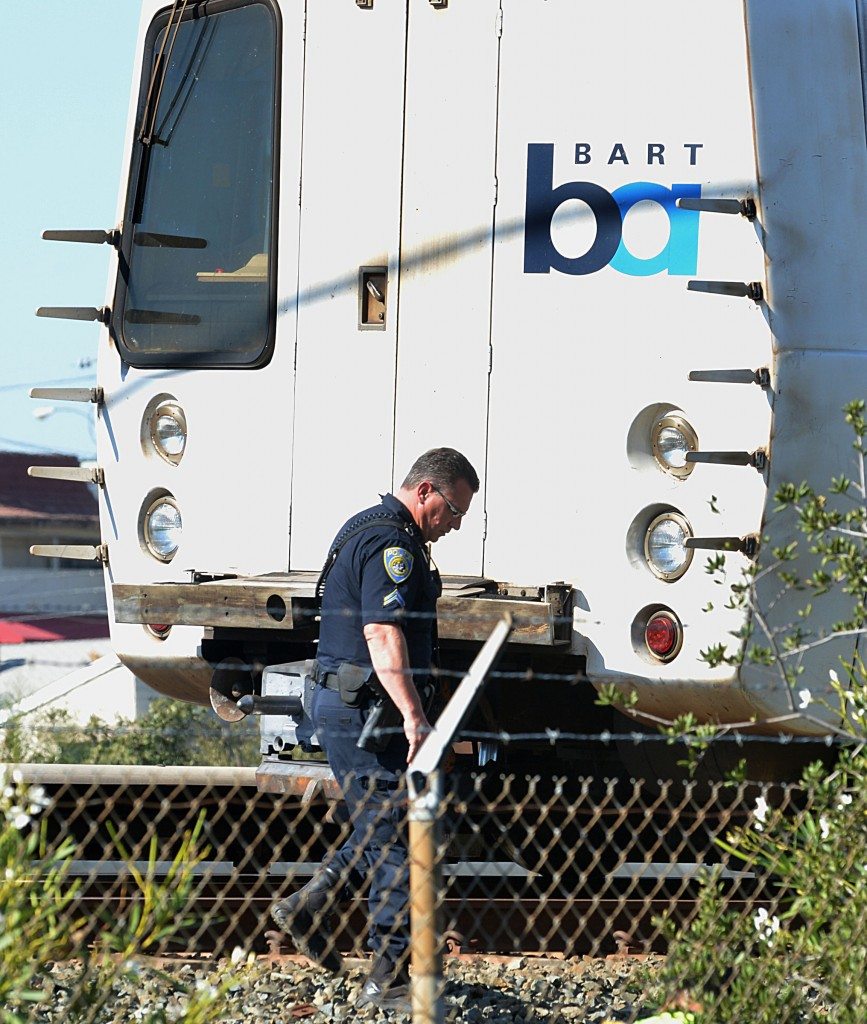 A BART police officer looks along the outside of a BART car that struck and killed two people along Jones Road in Walnut Creek, Calif., on Saturday, Oct. 19, 2013.