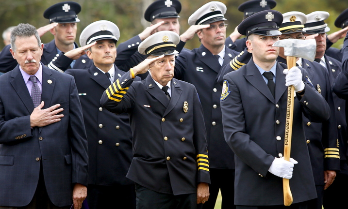 Members of the Portland Fire Department salute during the reading of those who died in the line of duty during the Portland Veteran Firemen's Association memorial service Sunday in South Portland.