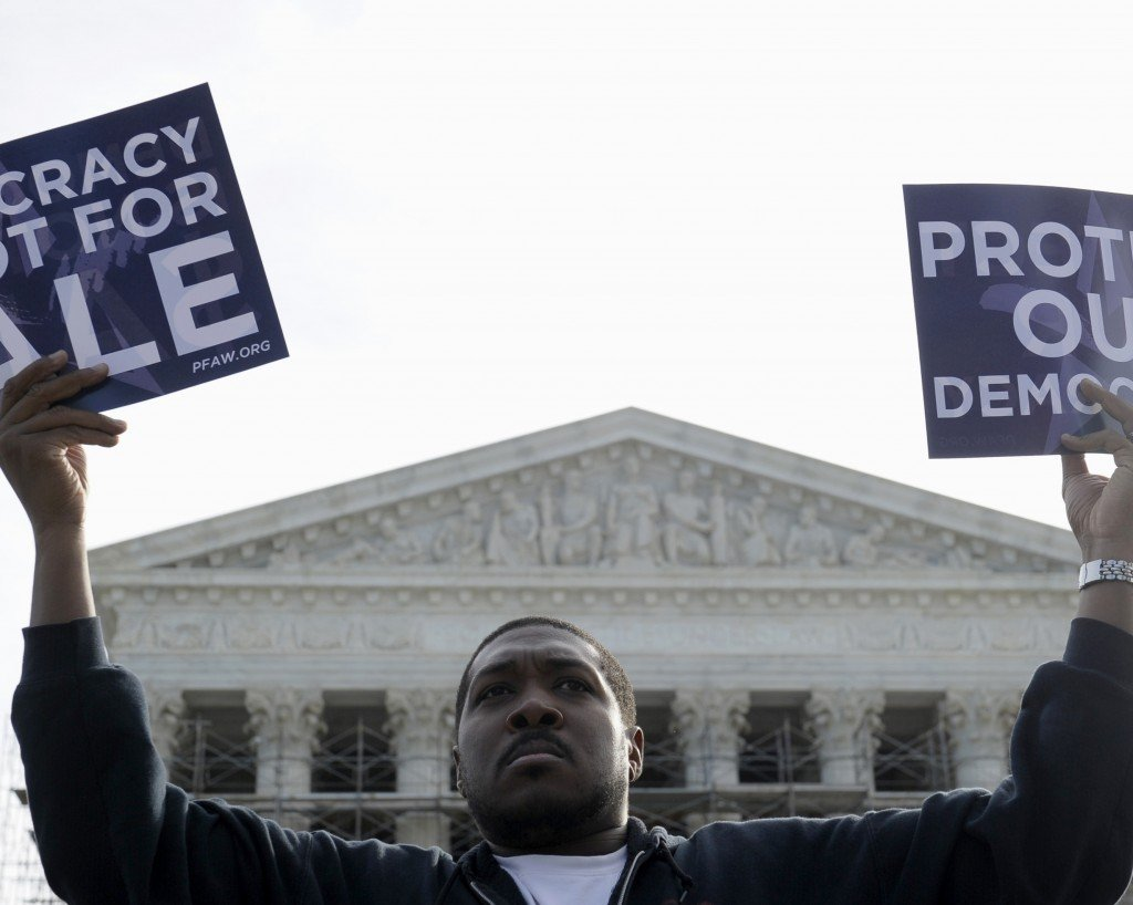 Cornell Woolridge of Windsor Mill, Md., protests Tuesday outside the Supreme Court in Washington as the court heard arguments on campaign finance.