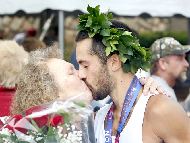 Rob Gomez of Saco receives a congratulations kiss from his mother, Connie, in Portland on Sunday, after winning the Maine Marathon on Sunday.