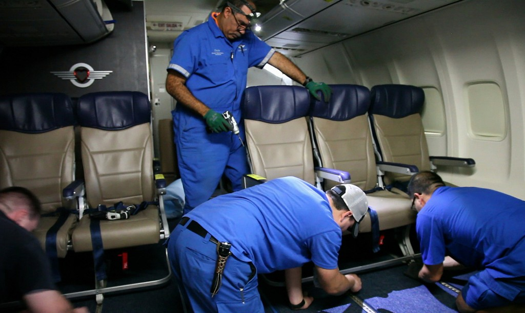Southwest Airlines aircraft technicians install skinnier seats on a 737 at the carrier's headquarters in Dallas. Southwest says passengers will have the same amount of legroom even though the new seats allow for another row aboard each plane.