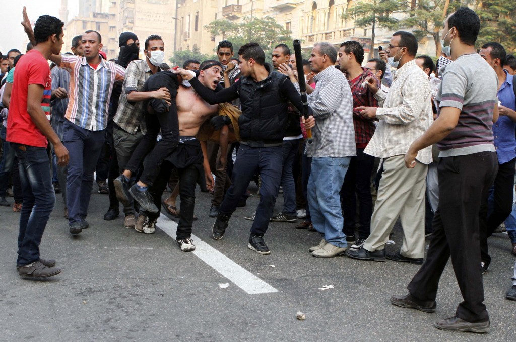 Egyptian security forces and civilians detain a supporter of ousted Egyptian President Mohammed Morsi in Cairo, Egypt, on Sunday. The deadly violence occurred during a holiday celebrating the 40th anniversary of the 1973 war with Israel.