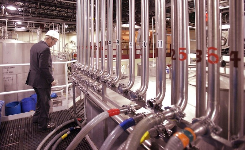 In this 2011 file photo, John Suczynski walks past a row of stainless steel pipes that transport alcohol to the bottling lines at White Rock Distilleries in Lewiston. Sazerac Co., a distiller draped in the history of New Orleans' French Quarter, will expand its reach to Maine with the purchase of the former White Rock bottling plant in Lewiston.