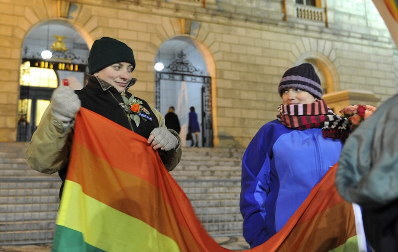 Amber Hardy of Portland and Amanda Poulin glance at each other as they unfurl a gay pride flag in front of Portland City Hall Friday, December 28, 2012 before the first same sex marriages were performed in Maine. Portland ranks among the U.S. cities with the highest concentration of households headed by same-sex couples, a new analysis of census data shows.