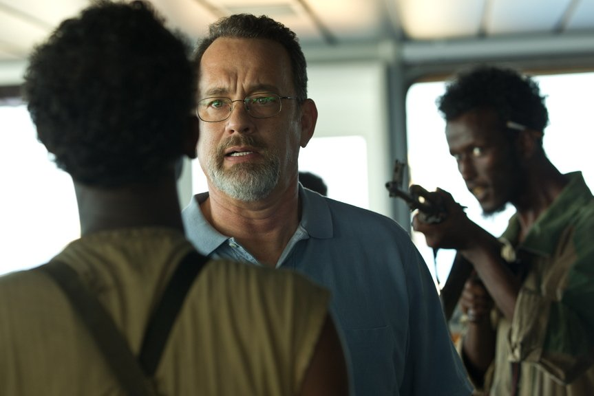 "Tom Hanks, center, deals with pirates in ""Captain Phillips,"" a film dramatizing the 2009 attack on the M.V. Maersk Alabama off the coast of Africa. Directed by Paul Greengrass, the movie is good enough to keep viewers on the edge of their seats to the end even though they probably already know how it turns out."