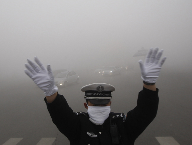 A traffic policeman signals to drivers during a smoggy day in Harbin, Heilongjiang province, on Monday. The second day of heavy smog has forced the closure of schools and highways.