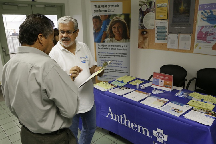Alberto Pizon, right, a representative of Anthem BlueCross BlueShield Latino Health Access group provides free information to Paulino Zarate, 65, left, on the new health options available during a health fair promoted at the Binational Health Week event held at the Mexican Consulate in Los Angeles Tuesday, Oct. 1, 2013. Thousands of Californians seeking to buy their own health insurance flooded call centers with questions and overloaded the state's online marketplace Tuesday on the first day of a new federal health care law that will dramatically change the way Americans buy health insurance.