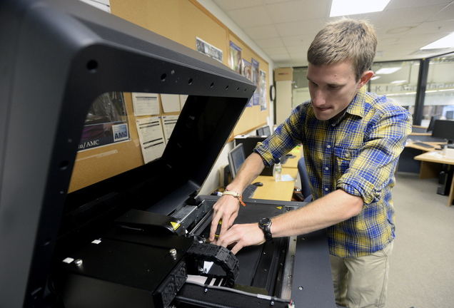 Christopher Dunn, a mechanical engineering student at the University of Southern Maine, removes an object he printed with a 3D printer. Experts in Maine say 3D printing can be used to make virtually anything.