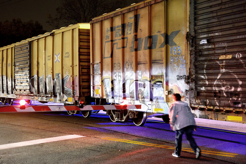 A parked freight train blocks a passing pedestrian following a fata accident along the stretch of train tracks between Forest Avenue and Irving Street in Portland on Wednesday, Oct. 17, 2013. A man who was walking along the tracks was struck and killed by a freight train Wednesday night, police said. When the freight train stopped, it blocked Forest Avenue from 7:15 to about 10 p.m.