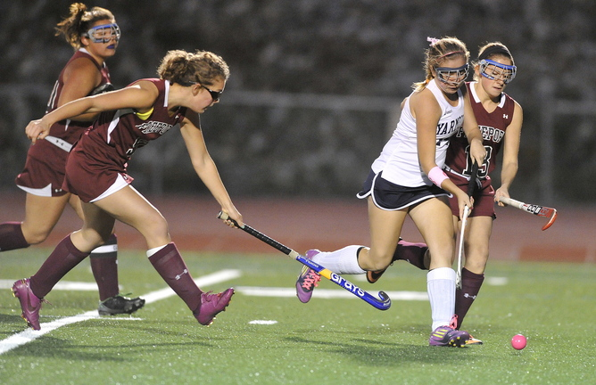 Haley Boydon of Yarmouth pushes the ball through the Freeport defense, attempting to rush past Abby Smith, right, during their Western Maine Conference field hockey game Tuesday night. Yarmouth scored twice in the second half at home for a 2-0 victory.