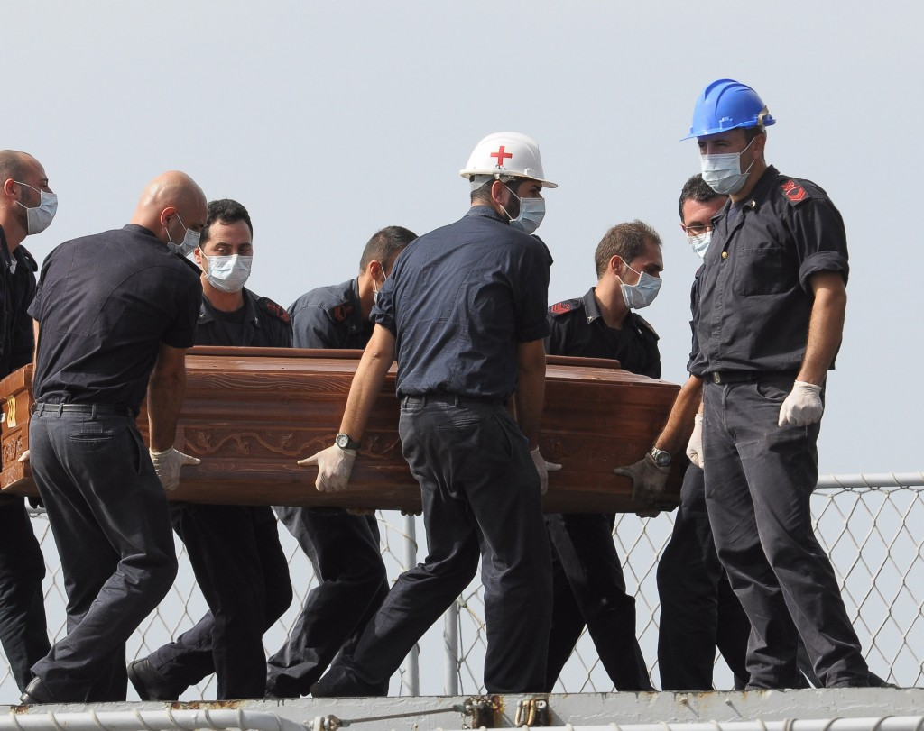 The casket of migrant who died when a packed fishing boat capsized in the Canal of Sicily is carried aboard a Italian Navy ship at the Lampedusa island harbor Saturday.
