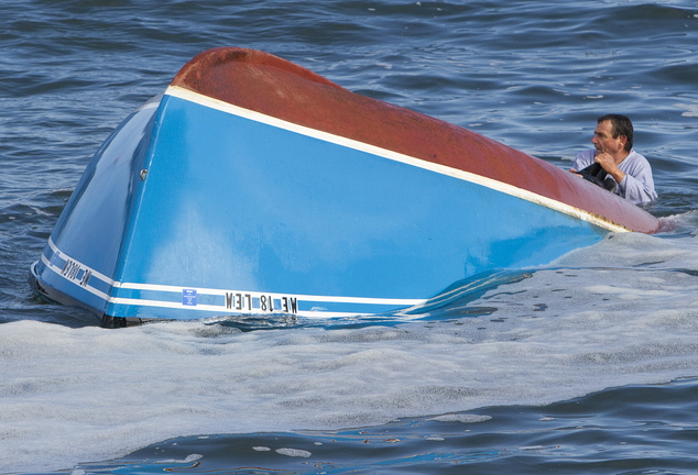 A fisherman from the boat that overturned in rough surf between Wells Beach and Drakes Island holds on to the capsized boat while awaiting rescue Sunday.