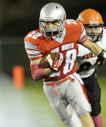 South Portland running back Joey DiBiase gets some running room after getting outside of Biddeford's Dan Copeland during Friday night's win in South Portland. The Red Riots improved to 5-2 on the season.