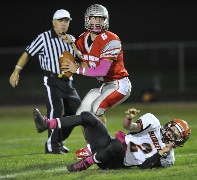 South Portland quarterback Duncan Preston shakes off the tackle of Biddeford's Corey Creeger and looks for an opening downfield during Friday's 55-24 win.