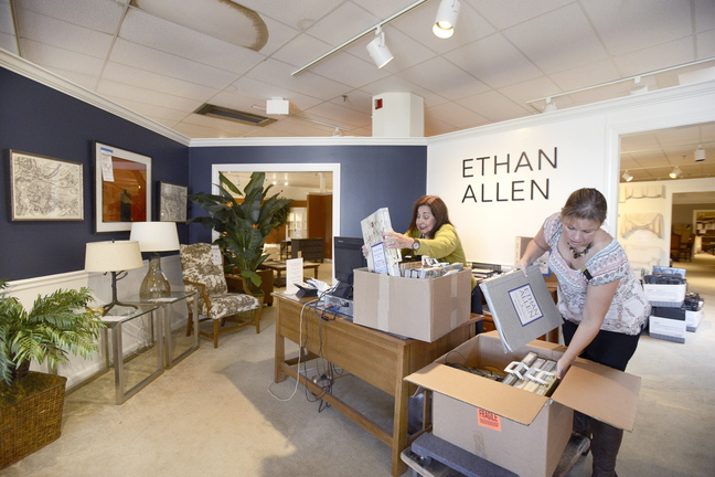 Employees Lenora Bourgeois and Julie Parent pack wallpaper books at the Ethan Allen furniture store in South Portland in preparation for their move into a new store in Portland.