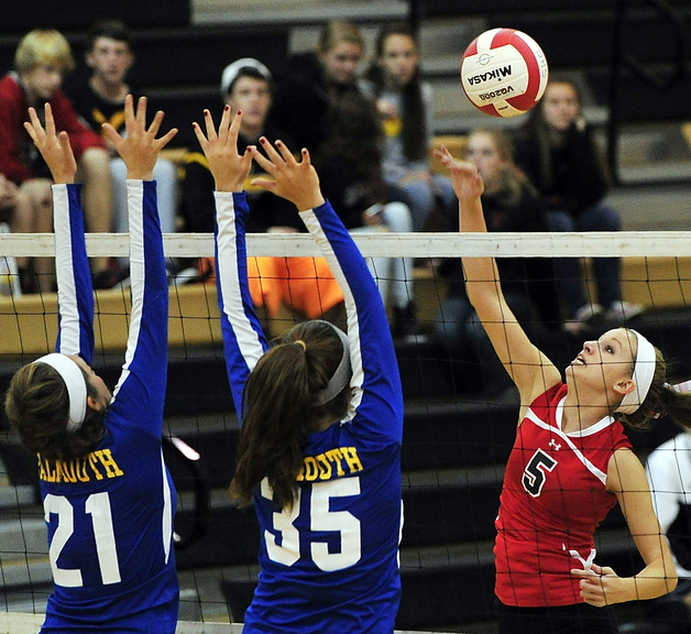 Natalie Foster of Scarborough hits over the defense of Falmouth's Katrina Meserve, left, and Ally Hickey during Monday's volleyball match in Scarborough, won by the host Red Storm, 21-25, 25-21, 25-18, 15-25, 15-5.