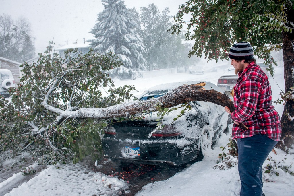 Zack Ruml, 20, of Rapid City, S.D, lifts a heavy crab apple tree branch off of his 1998 Pontiac Gran Prix on Friday. The branch smashed the rear window and dented the trunk of the car. Trees in the city are still fully leaved and the heavy snow is breaking trees throughout the city. Blizzards rolled into parts of Wyoming and South Dakota on Friday, bringing the snow-savvy states to an unseasonably early winter standstill.