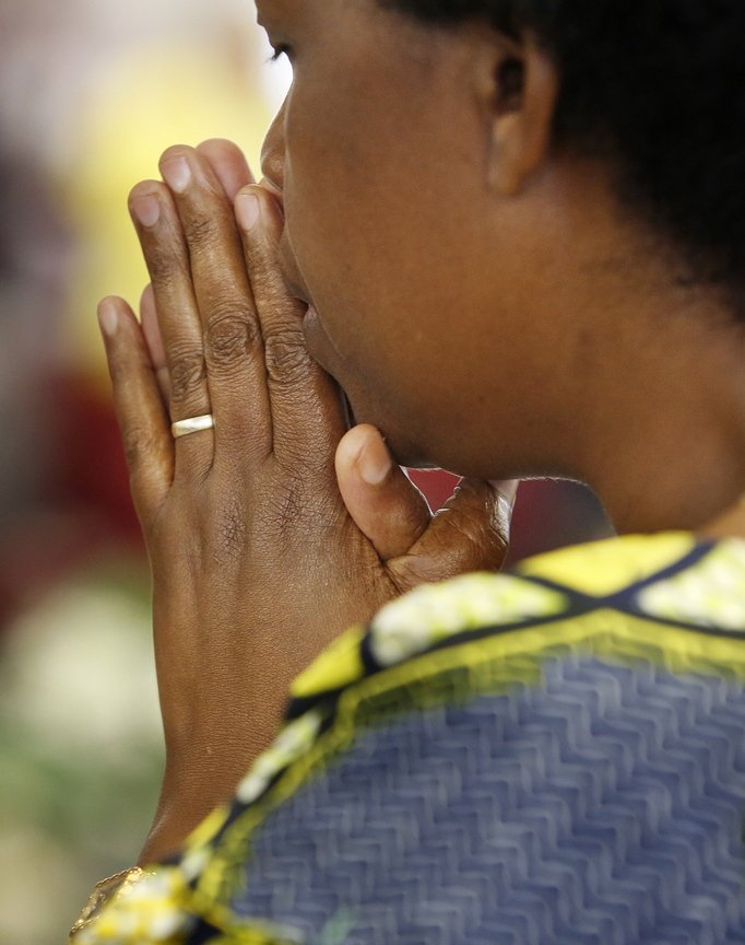 "A woman prays at the church filled with ""new Americans."""