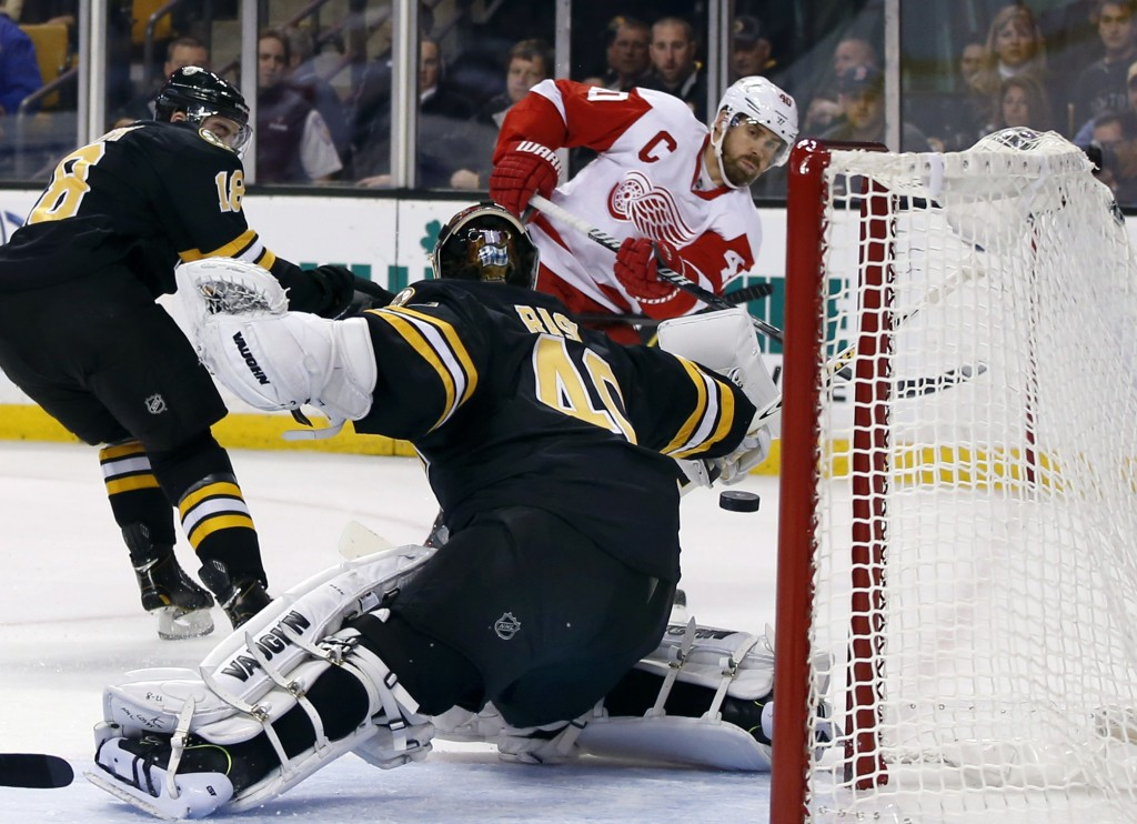 Detroit Red Wings center Henrik Zetterberg (40) shoots and scores against Boston Bruins goalie Tuukka Rask (40) as Bruins right wing Reilly Smith (18) defends, at left, in the first period of an NHL hockey game in Boston, Monday, Oct. 14, 2013.