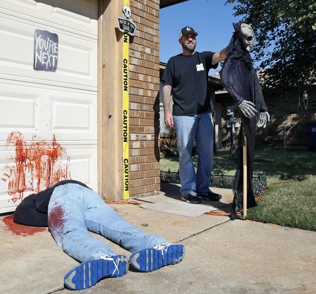 Johnnie Mullins stands Thursday with his controversial Halloween display featuring headless dummies dressed in his work clothes at his home in Mustang, Okla.