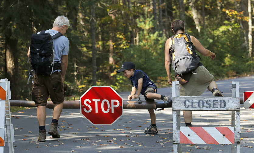 Gabe Souza/Staff Photographer Titus Steinberg, 5, of Herne, Germany, hops over the gate at Acadia National Park's Echo Lake in Southwest Harbor Wednesday, October 2, 2013, along with his parents Oliver, at left, and Ramona, at right. The family was one of a handful of visitors who wouldn't let the closure of Acadia National Park stop them from entering it.