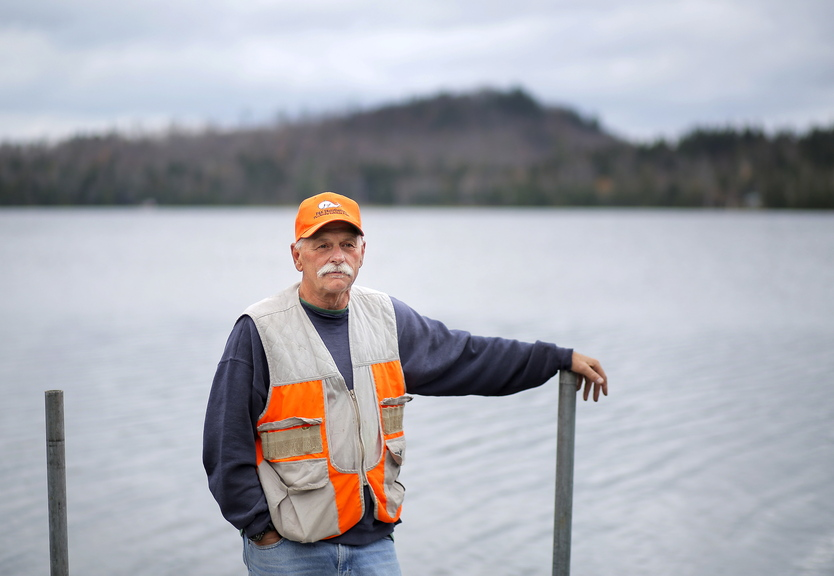 "Rodney Jones of Fort Fairfield stands on the dock of his wife's family's camp on Number Nine Lake in Township 9, Range 3 in central Aroostook County. Jones said he opposes a wind farm proposed by EDP Renewables. ""Nobody wants to see windmills along the lake,"" he said."