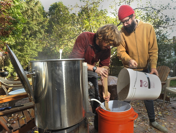 Dilger and Boguski stir in ground barley to create the mash mixture that they will use when making their next batch of home brew.