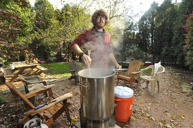 Craig Dilger heats up water used in making the mash mixture for his next batch of home brew beer at his Portland apartment.