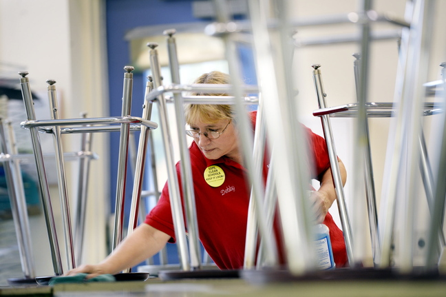 "Debby Bean, custodian at Scarborough Middle School, cleans desks in a classroom after the students have gone home for the day Monday. ""I would like the schools to stay safe and clean and keep the jobs local,"" she says."