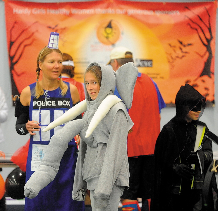 "Alison Stabins, 11, center, dressed as an elephant, and her mother, Amy, dressed as Tardis from ""Dr. Who,"" await the start of the Freaky 5K Fun Run sponsored last Saturday by Hardy Girls Healthy Women at Colby College in Waterville. The event was organized to encourage girls to come up with creative and scary Halloween costumes instead of stereotypical or sexually overt ones."