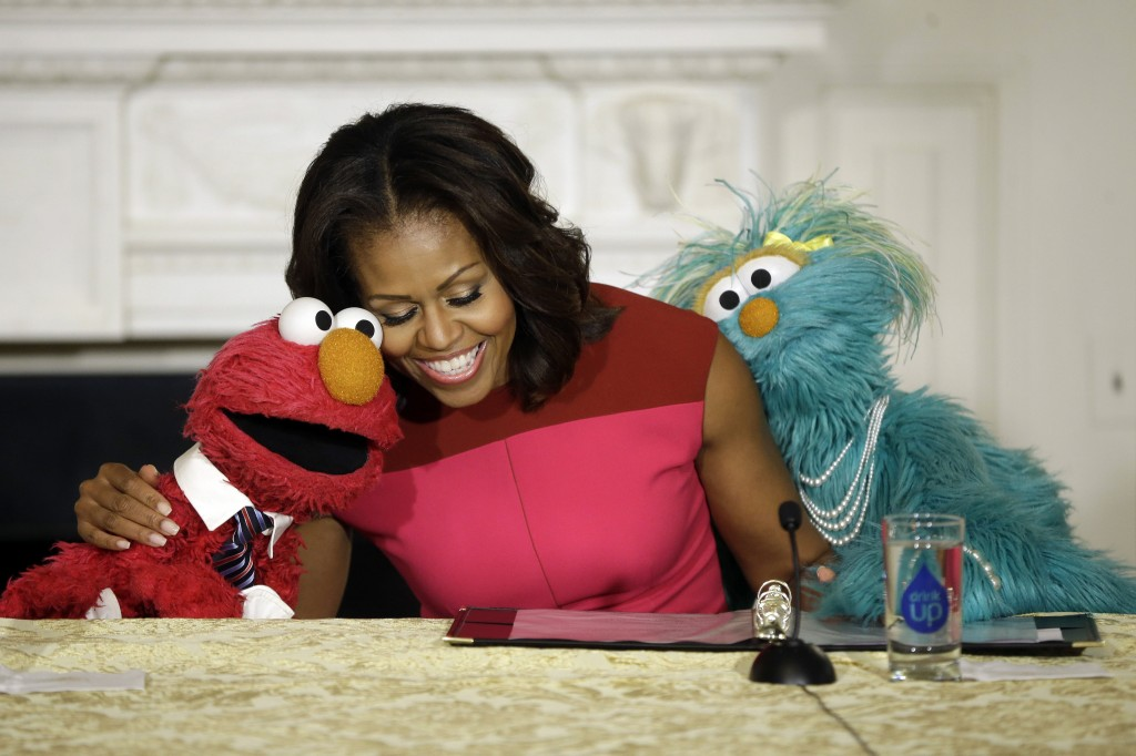 The Associated Press First lady Michelle Obama shares a hug with PBS Sesame Street's characters Elmo, left, and Rosita as they help promote eating fresh fruits and vegetables to children at an event in the State Dining Room of the White House in Washington on Wednesday.