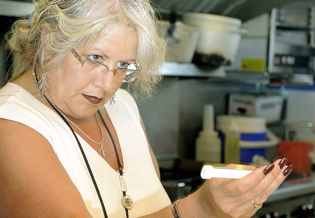 Michele Sturgeon checks the temperature of food at a Portland restaurant. A letter writer says the city should be ashamed for paying her to quit as health inspector.