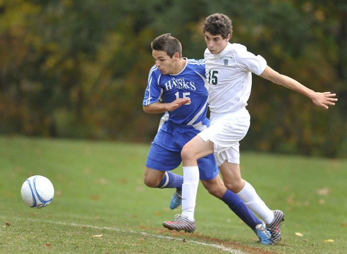 Aaron Lee of Waynflete tries to hold back Sacopee Valley's Ryan Moulton as they chase the ball.