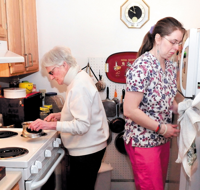 Seton Village resident Marie Rouleau, left, and personal support specialist Zandra Luce work in the kitchen preparing a meal March 25. Rouleau is on a waiting list for the Meals on Wheels program.