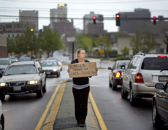 Alison Prior of Portland panhandles at the corner of Preble Street and Marginal Way in May. Prior is one of three residents suing the city over its ordinance barring people from standing in road medians.