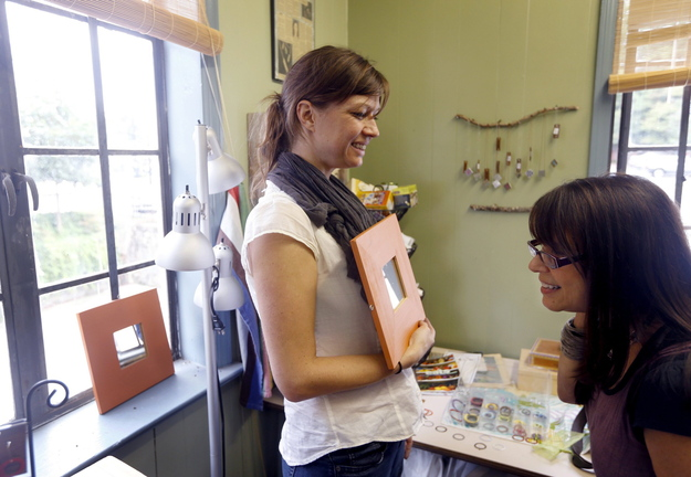Debbie Rothstein, right, checks out laminate hoop earrings made by Kiona van Rhee, owner of Lucky Accessories, in van Rhee's studio in Raleigh, N.C. Van Rhee uses her Etsy shop as her retail outlet for her handmade items.