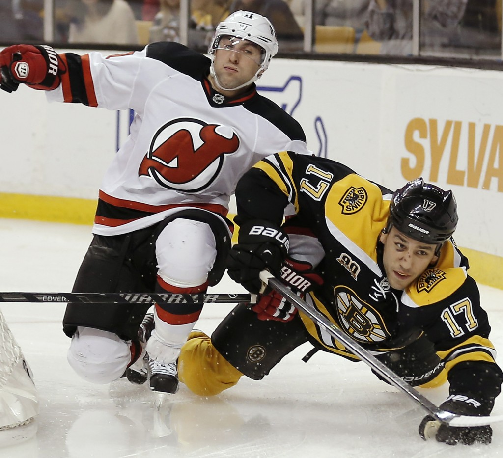 New Jersey Devils' Stephen Gionta, left, spills Boston Bruins' Milan Lucic during the second period of Saturday's game in Boston, won by the Devils on two late goals.