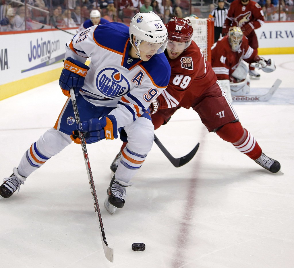 Edmonton's Ales Hemsky shields the puck from Phoenix's Mikkel Boedker during Saturday's game in Glendale, Ariz., won by the Coyotes.