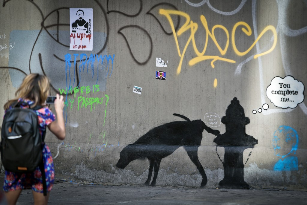 Graffiti by the secretive British artist Banksy, featuring a dog and a fire hydrant, draws attention on 24th Street in New York City earlier this month.