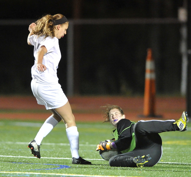 Freeport keeper Livvy Dimick sprawls to the turf to gather the ball in front of Yarmouth's Katherine Clemmer. The Falcons will visit top-seeded Cape Elizabeth in the semifinals.