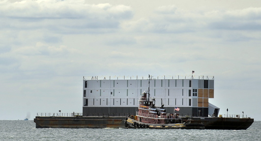 A tugboat leads a barge carrying a mystery structure down the Thames River after it left New London, Conn., on Wednesday bound for Portland.