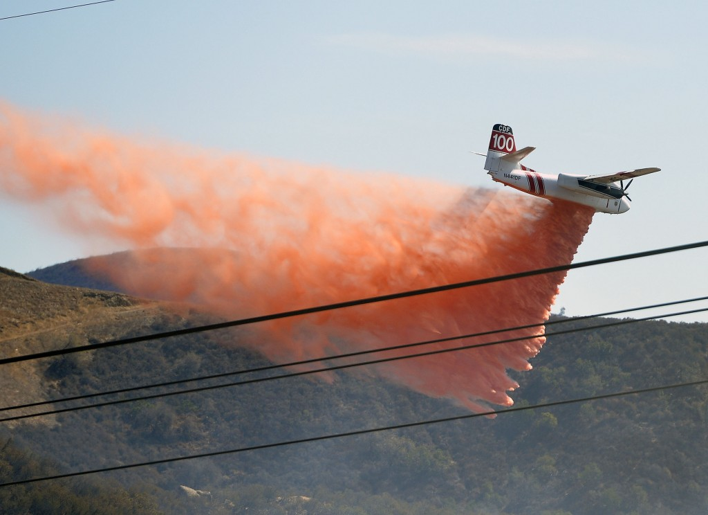 A California Department of Forestry firefighting aircraft preventatively drops retardant on a ridge above Baker Canyon in Orange County, Calif. Sunday, Oct. 6, 2013. The mulch pile fire reported late Sunday morning quickly spread to surrounding wild vegetation, said Orange County Fire Authority Capt. Steve Concialdi. No homes were threatened.