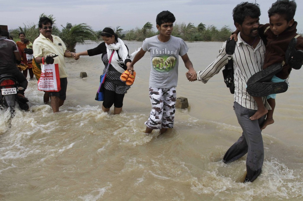 People hold hands as they cross a flooded road to return to their respective villages near Gopalpur, Orissa state, India, on Sunday. Like many others, they survived Cyclone Phailin by heeding evacuation orders.