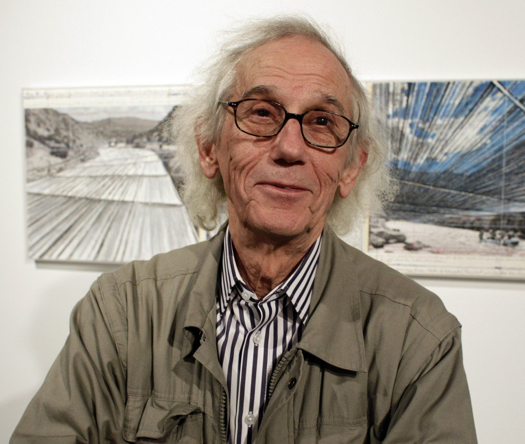 """Christo stands in front of his proposed """"Over the River"""" project at the Metropolitan State University Center for Visual Art in Denver. He says he welcomes debate over what is appropriate."""